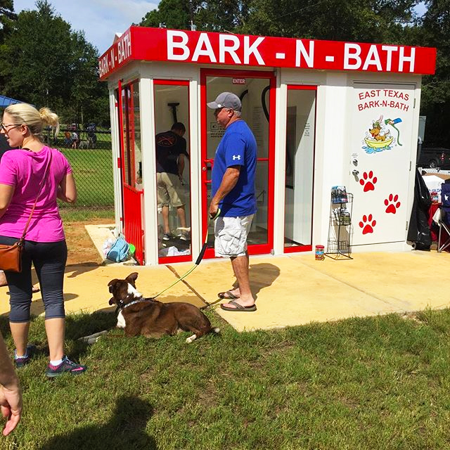 People lined up outside of the pet wash at the dog park waiting for their turn with their dogs.